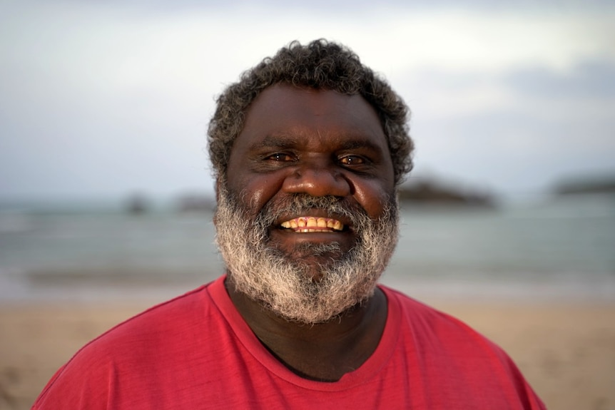A man in a red t-shirt smiles into the camera.