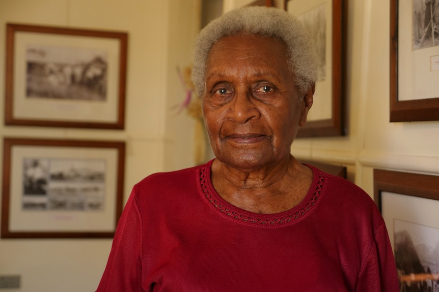 Aunty Doris straight-faced, red shirt, historic images on wall behind.