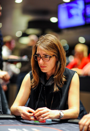 Alex O'Brien, with glasses, shoulder-length brown hair and dark blouse, sits at poker table holding chips, looking focused.