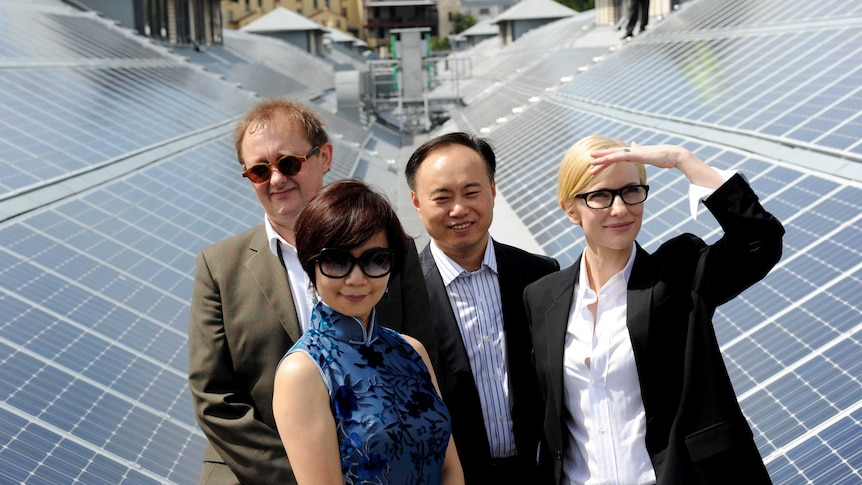 Four people stand in front of solar panels