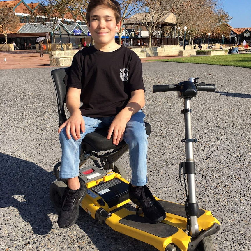 Coby Antonio sits in a yellow motorised scooter wearing a black t-shirt, jeans and black shoes.