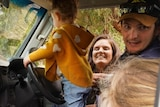 A man laughs inside his ute with two young girls with his wife leaning in through the window.