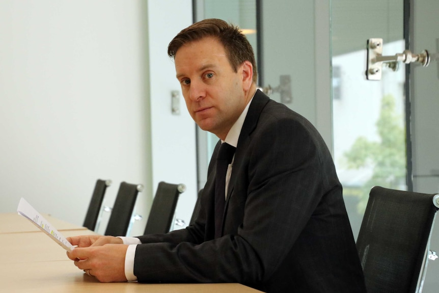 Chris Kent looks at the camera while sitting at a row of desks in a boardroom.