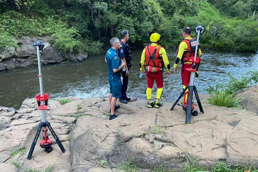 police, ambulance and swift water rescue crews examine a waterfall where a man drowned