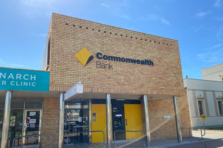 A cream brick building with Commonwealth Bank sign and yellow windows and ATM on a country street.