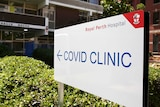 """A large white sign says """"COVID Clinic"""" and has the Royal Perth Hospital logo on it."""