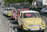Trabant cars drive in front of the remains of the 'Mauer' frontier wall