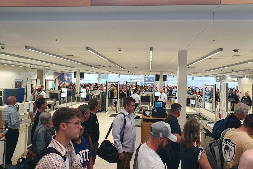 Passengers standing in lines evacuate Adelaide Airport.