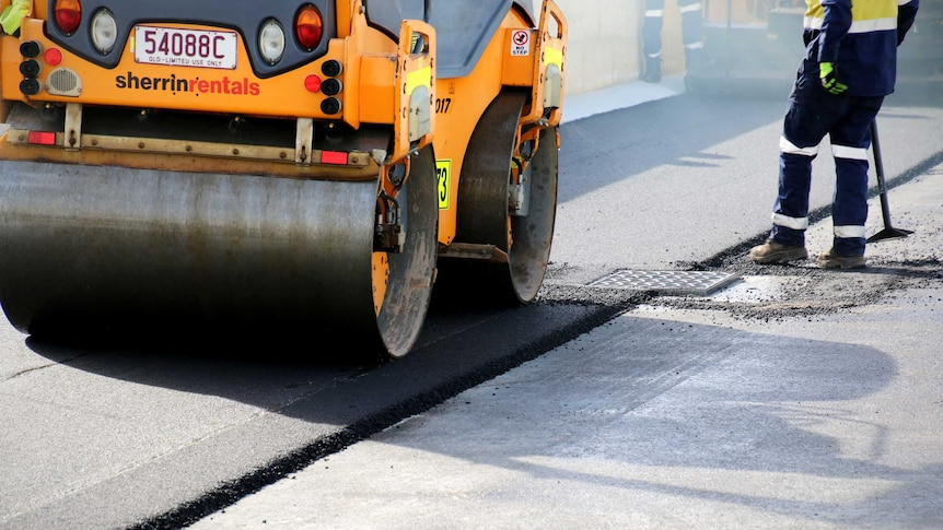 A steam roller paves a new road