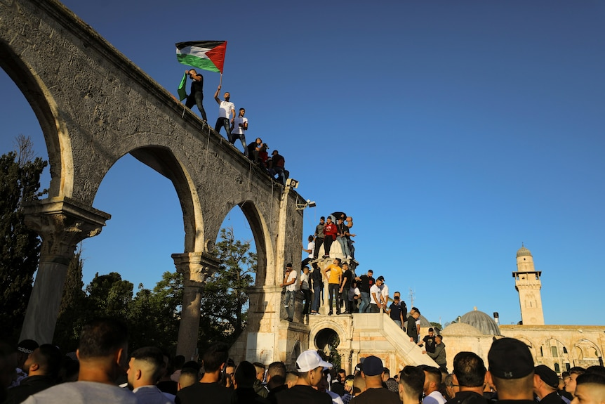 People wave Palestinian flags while standing on a stone arch at al-Aqsa mosque compound