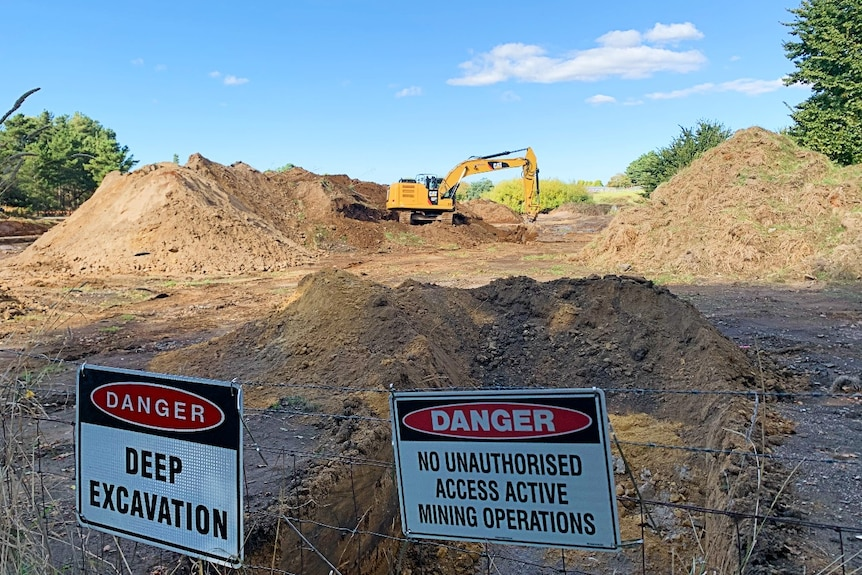 An excavator digs behind a fence with warning signs