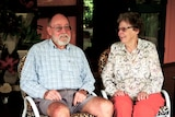 Two people in their 80s sit on a verandah, neither looks directly at the camera