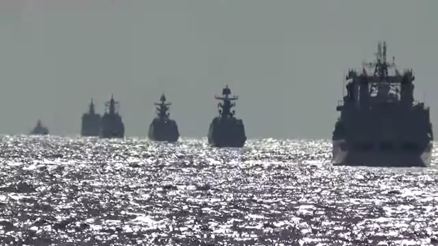 A silouhette shot of six ships sailing away from the camera at dusk