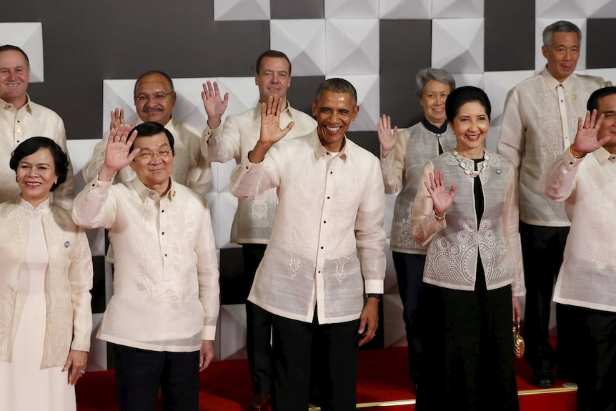 Leaders wave together in traditional dress at apec summit