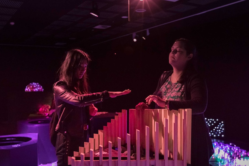 Two young girls hover their hands over an interactive art installation.