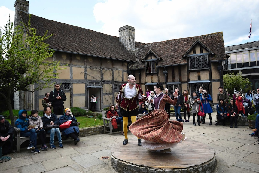 Tourists watch actors perform at the house where William Shakespeare was born.