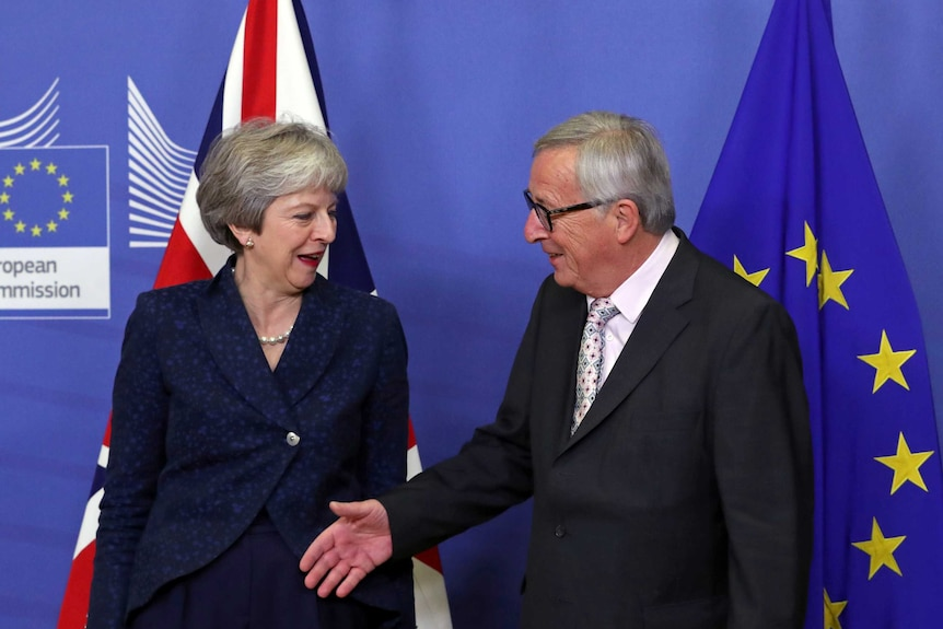 A woman smiles while a man extends his hand towards her