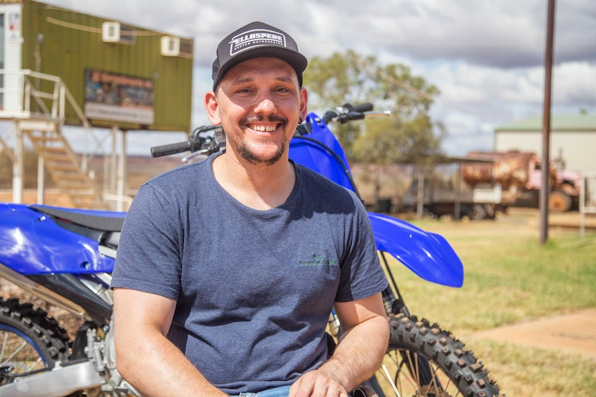 A man sits in front of a dirt bike.