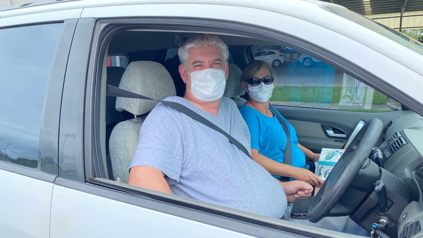 A man and a woman sit in a car wearing face masks.