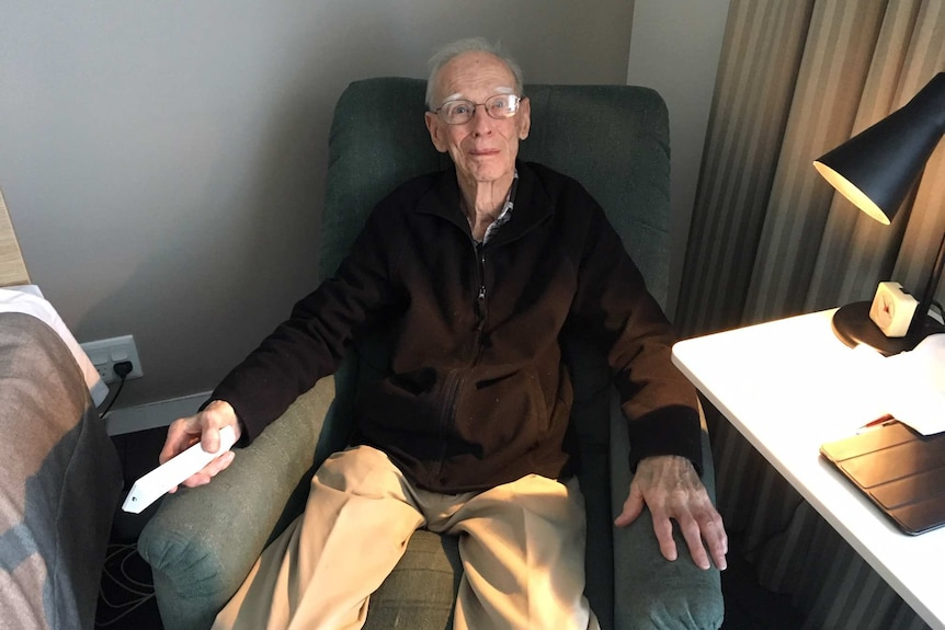 An elderly man sitting in a chair holding a remote control