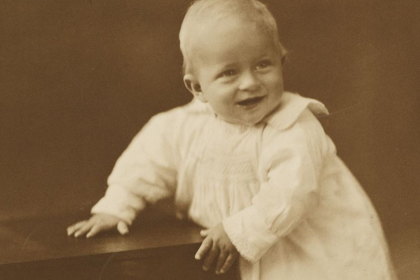 A sepia photograph of infant Prince Philip in a white dress, standing and holding onto a small table.