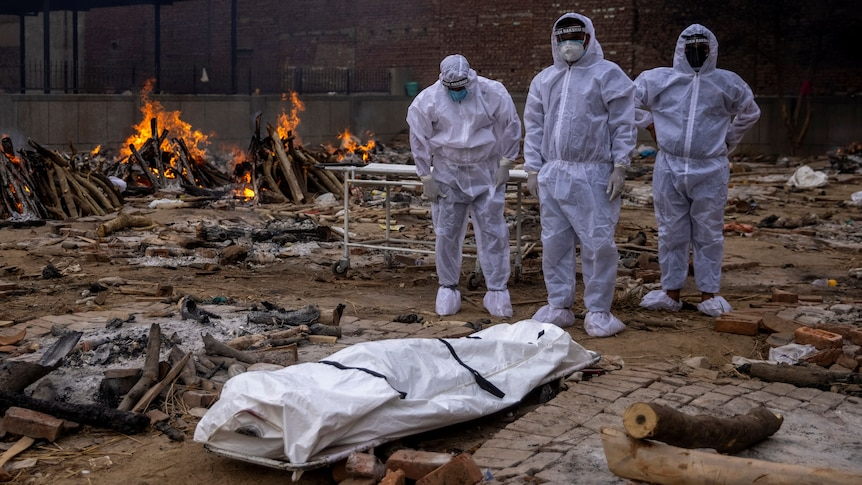 Three men in protective suits stand next to a body covered on the floor as fire burns behind them.
