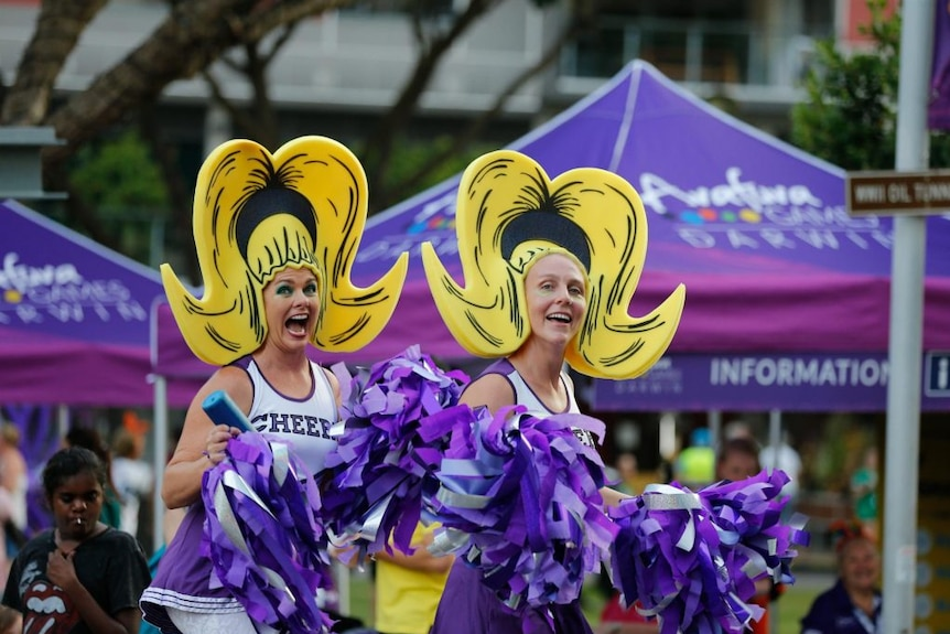 Women in cheerleading outfits pose, grinning.