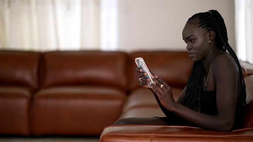 Unice Wani looks at her phone as she sits on a couch.