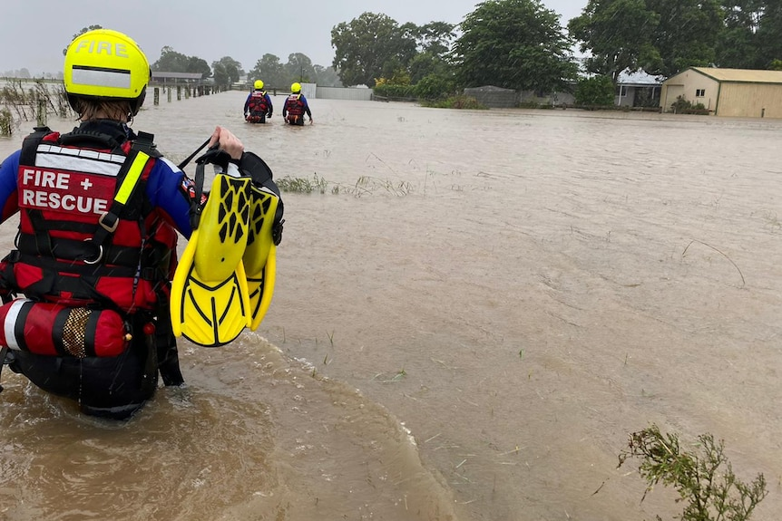 Three people wearing wet suits and helmets wade through waist deep floodwaters.