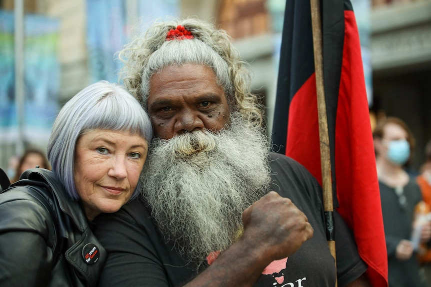 A white woman with short hair next to an Aboriginal man with a grey bear and hair, his fist clenched and a holding a flag.