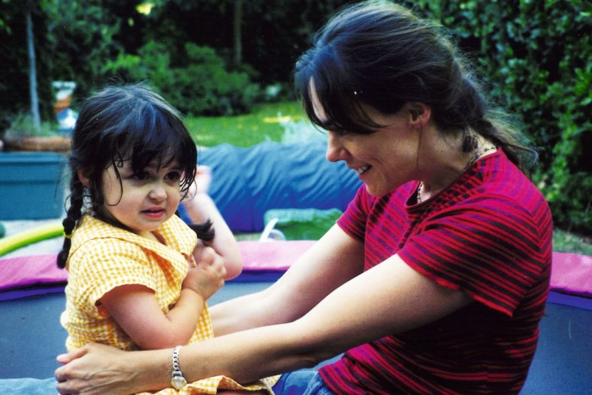 A woman and her little girl, who has pigtails in her hair, sit on a trampoline