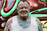 Man with colourful full body and face tattoos.
