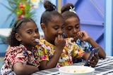 Three girls looking at their mobile phones at a community celebration.