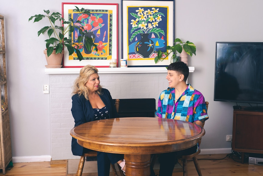A woman wearing a dark blazer sits across a table from a young person wearing a bright shirt