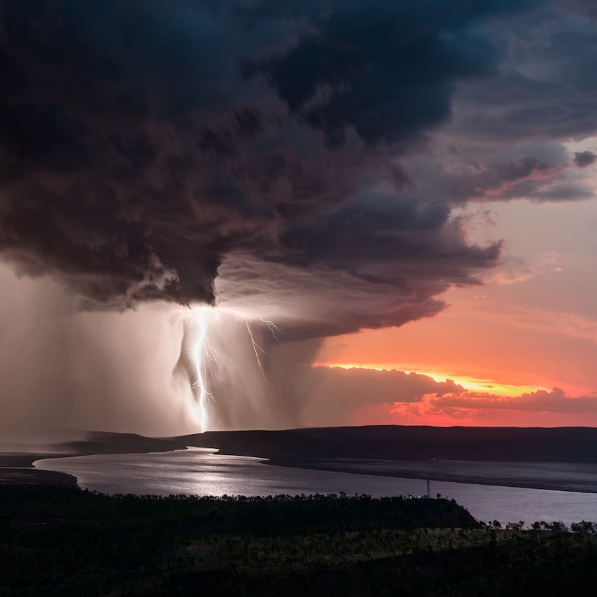 A storm rips through a red sunrise.