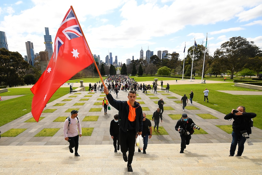 A protester holds the Red Ensign Australian flag during a protest
