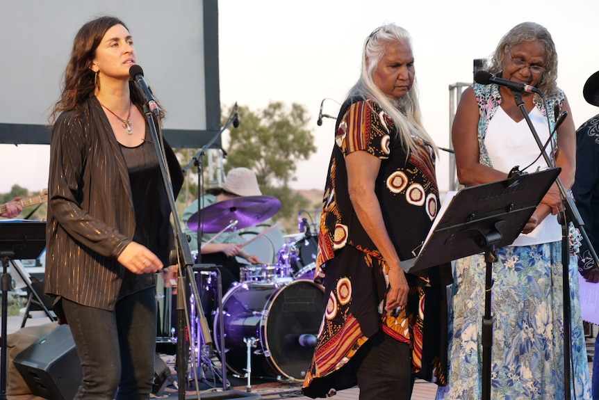 Three women singing at a concert.