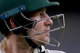 Cameron Bancroft looks to the side with his bat tucked under his arm and his batting helmet on
