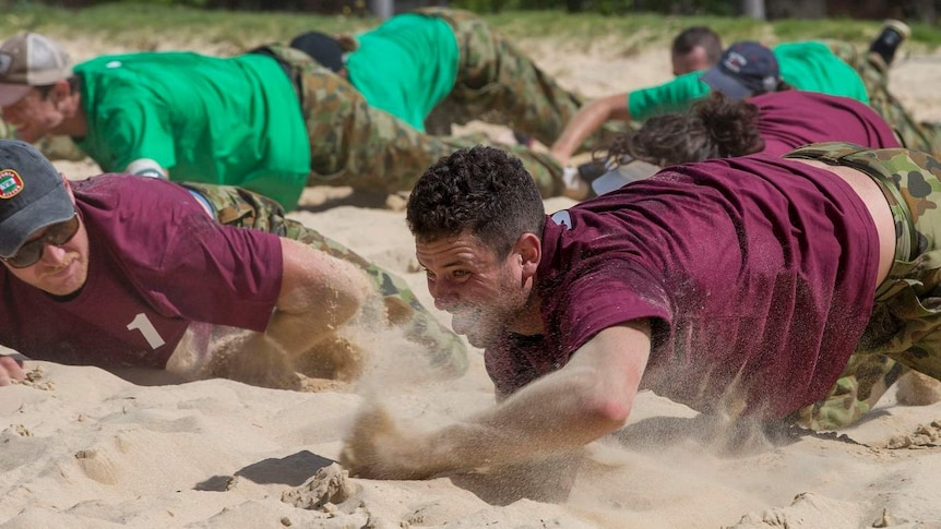 A man in a coloured t-shirt army crawls through sand as another man looks on.