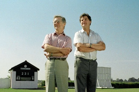 Two men stand on grass with arms folded, with a cricket scoreboard and sightscreen in background.
