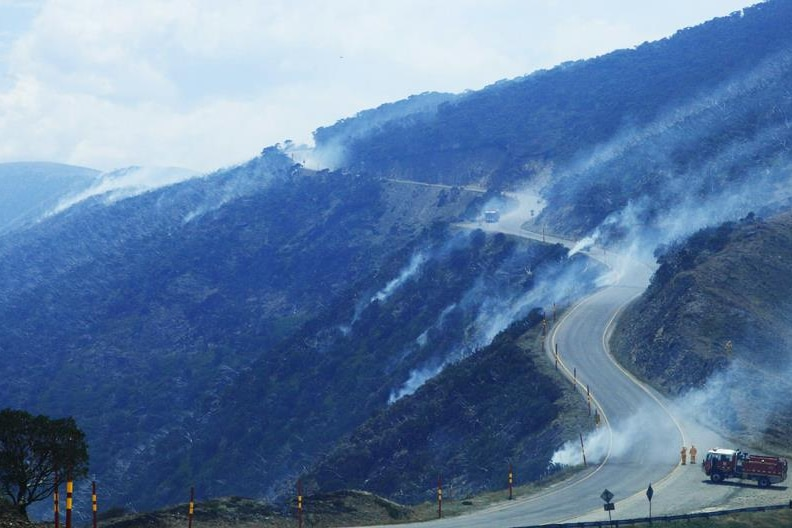 Smoke comes from a steep mountainside, and firefighters are stationed on a road at the top of a mountain with a truck