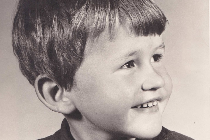 A young boy has his head turned slightly and smiles.