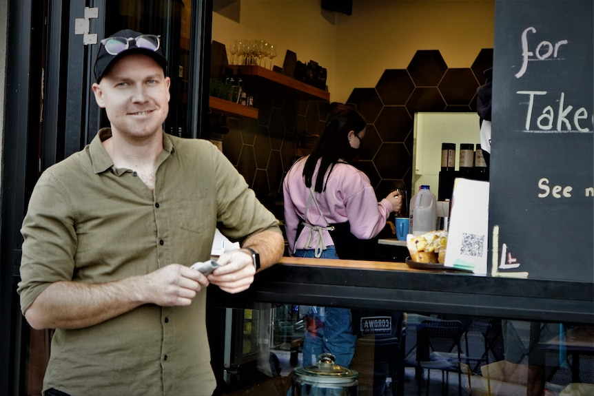 man standing at a coffee window