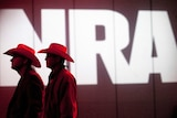 Two men with cowboy hats stand in front of a sign saying NRA.