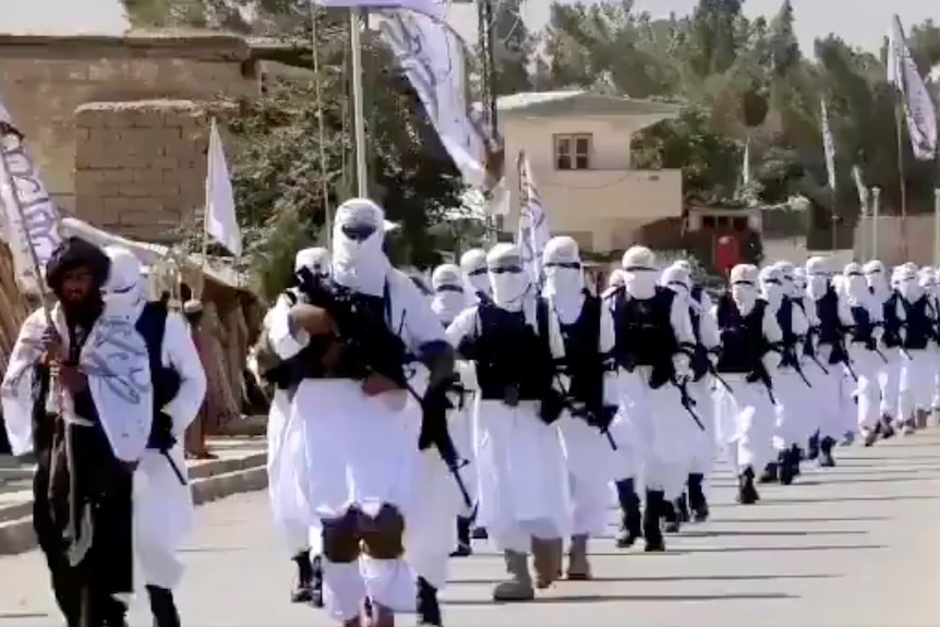 Dozens of Taliban fighters march in white uniforms down a street