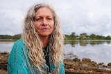 portrait of a woman, not smiling, long grey curly hair in a blue shawl by a glassy river