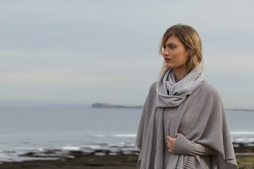 A merino lamb and woman wearing woollen clothing on the beach