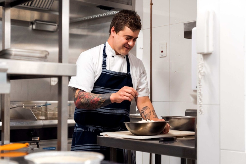 A chef works in a restaurant kitchen wearing a blue apron and white chef's shirt and leaning over a silver bowl.