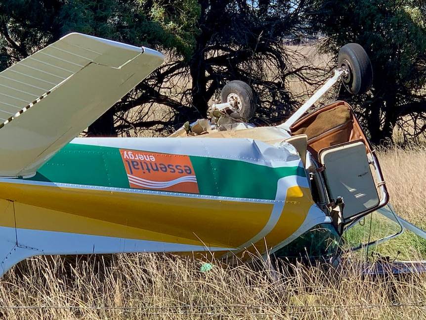 Close up of a small plane upside down in the field.