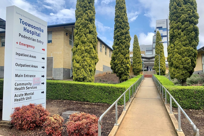 The outside of the Toowoomba Hospital, including a sign and walkway lined with trees.